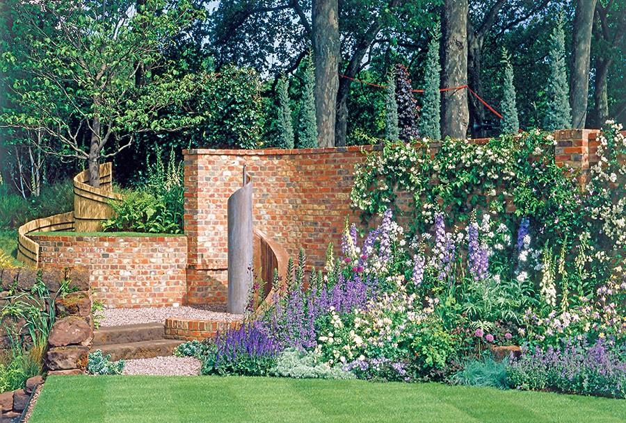 En hel trädgård skapad efter det gyllene snittet, med spiralen som utgångspunkt. Skärningspunkten är tegelpelaren. Rabatterna har fått mjukt svängda former som bäddar in gräsmatten. Foto. K. Engstrand