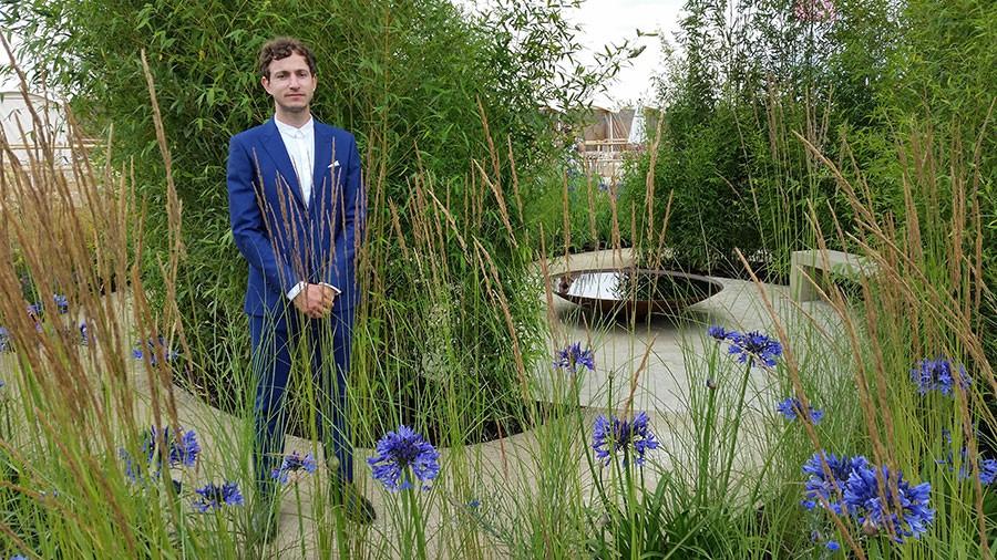 Tom Massey i sin trädgård, iklädd kostym som matchar Afrkas blå lilja!  Foto: Kerstin Engstrand